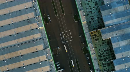 heliport : aerial view helicopter landing pad on road with driving lorries between large warehouses with metal roofs Stock Footage