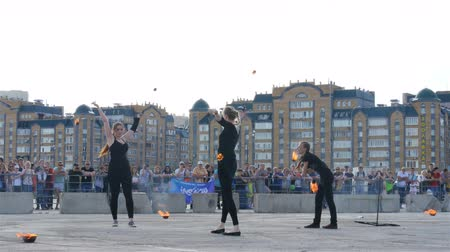 talentenjacht : KAZAN, TATARSTAN  RUSSIA - OCTOBER 27 2017: Talented athletic girls in black perform expressive fire show on city square on people and modern buildings on October 27 in Kazan Stockvideo