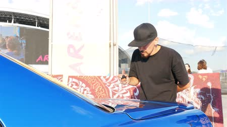 decorador : KAZAN, TATARSTAN  RUSSIA - NOVEMBER 08 2017: Closeup capable artist decorates blue modern car with abstract patterns using special tool on square on November 08 in Kazan Stock Footage
