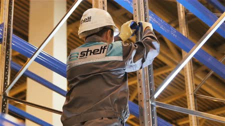 entire frame : KAZAN, TATARSTAN  RUSSIA - OCTOBER 25 2017: Closeup camera rotates around worker in uniform with Shelf logo fixing structure metal part on October 25 in Kazan
