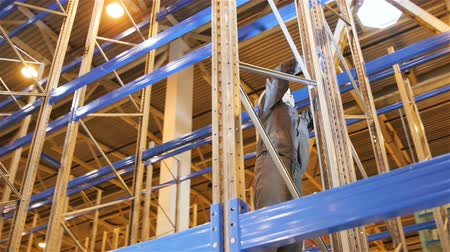 installation lectrique : KAZAN, TATARSTAN  RUSSIA - OCTOBER 25 2017: Closeup professional worker in outfit fixes rack metal part standing on blue lath at height on October 25 in Kazan