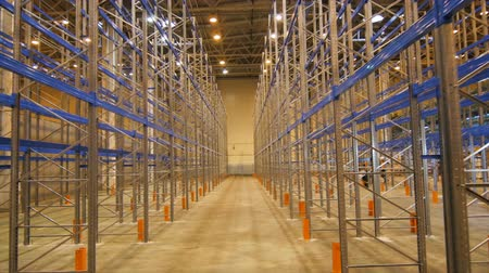 associados : camera moves from ceiling to floor along specious warehouse for finished goods storage associated with manufacturing