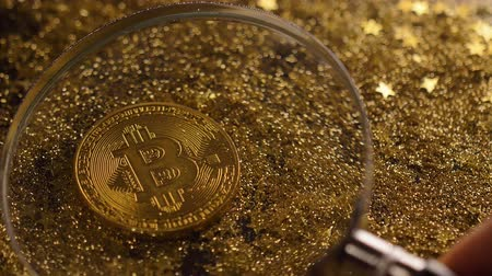 nagyítóüveg : macro golden coin under magnifying glass made by peer-to-peer payment system bitcoin against sparkles