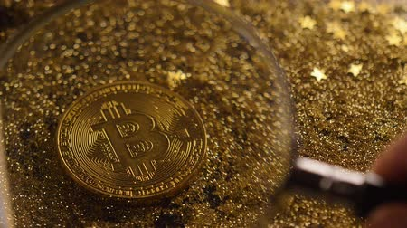 lupa : macro magnifier moves slowly away and shows gorgeous gold bitcoin real model among sparkles Wideo