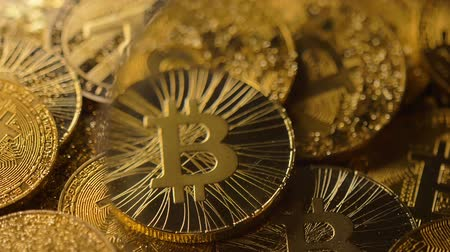 magnifier : macro view through magnifier on large sparkling bitcoin real model pile covered with gold dust Stock Footage
