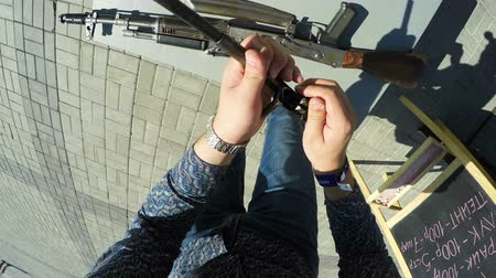 difficults : KAZAN, TATARSTAN  RUSSIA - NOVEMBER 14 2017: Top view unskilful man in jeans and shirt reassembles with difficulty disassembled military weapon on festival on November 14 in Kazan
