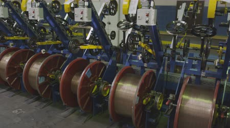 vasalás : closeup camera moves along factory department and shows machines reeling threads on bobbins