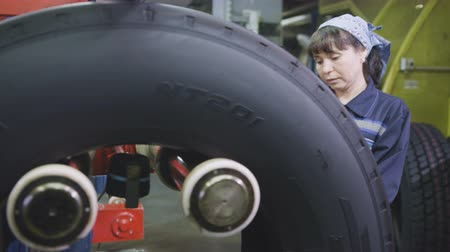 határozza meg : KAZAN, TATARSTAN  RUSSIA - SEPTEMBER 12 2017: Closeup employee in outfit puts rubber tire on two rising equipment shafts