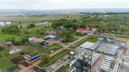 rurociąg : panorama gas refinery complex with towers and reservoirs against the village and large green meadow