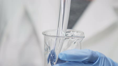 crude : closeup of a skilled lab assistant in blue gloves pours clear mucus into lab in modern researching laboratory