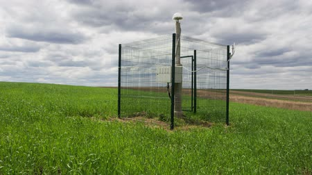 field measurements : new seismological equipment behind metal grid fence among fresh field with grass on cloudy day