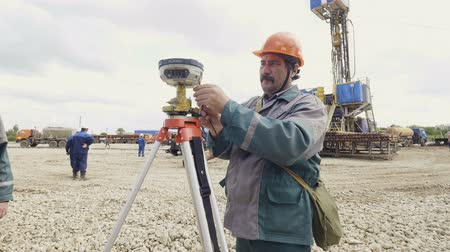 field measurements : KAZAN, TATARSTAN  RUSSIA - AUGUST 15 2017: Employee with a mustache in helmet and uniform connects wire to survey equipment on tripod against cranes on August 15 in Kazan