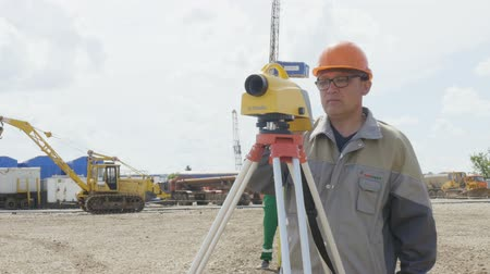 field measurements : KAZAN, TATARSTAN  RUSSIA - AUGUST 15 2017: Professional engineer in glasses and helmet stands at theodolite tripod on a large scale on August 15 in Kazan