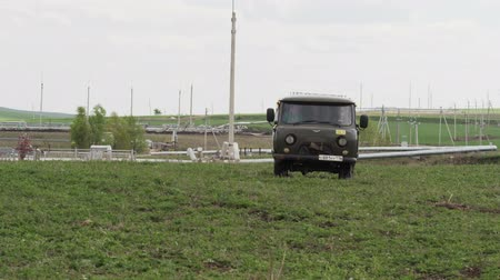 levou : KAZAN, TATARSTAN  RUSSIA - AUGUST 22 2017: Big car stops on oilfield and fuel workers in outfit take out stuff and put on grass under overcast sky on August 22 in Kazan