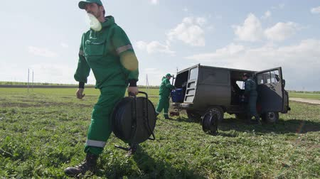 field measurements : KAZAN, TATARSTAN  RUSSIA - AUGUST 23 2017: Worker in green uniform and cap carrying large bobbin with wire along field and men taking tools out of car on August 23 in Kazan