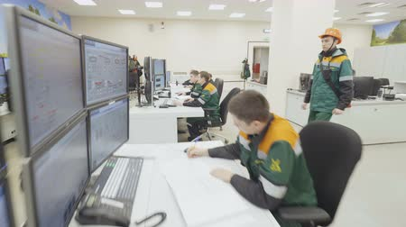 controlroom : KAZAN, TATARSTAN  RUSLAND - SEPTEMBER 19 2017: Close up van mensen die een baan bij computers en man in helm met een oranje zak collectie op 19 september in Kazan doen