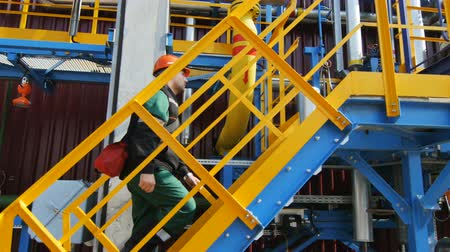 hydrocarbon : KAZAN, TATARSTAN  RUSSIA - SEPTEMBER 27 2017: Closeup oil production factory employee with crossbody bag climbs up stairs to processing equipment on September 27 in Kazan Stock Footage