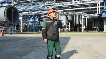 hydrocarbon : KAZAN, TATARSTAN  RUSSIA - SEPTEMBER 27 2017: Closeup of man in uniform controls manufacturing process and reports using radio set on petroleum company territory on September 27 in Kazan