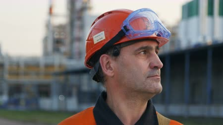 hydrocarbon : KAZAN, TATARSTAN  RUSSIA - SEPTEMBER 27 2017: Closeup of a serious worker portrait inspects huge heavy industry on September 27 in Kazan
