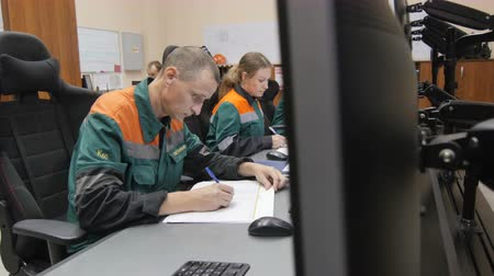 hydrocarbon : KAZAN, TATARSTAN  RUSSIA - SEPTEMBER 27 2017: Closeup gas company staff in uniforms sits at computers controlling oil processing and writes down in list on September 27 in Kazan