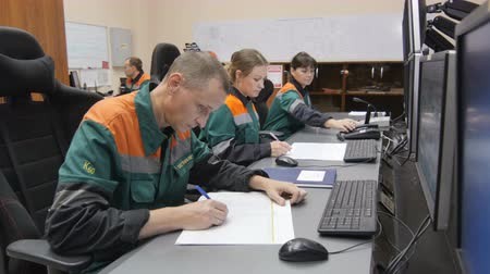 petroleum refinery : KAZAN, TATARSTAN  RUSSIA - SEPTEMBER 27 2017: Closeup of petrochemical plant workers sit at computers and perform work writing down data from monitors on September 27 in Kazan Stock Footage