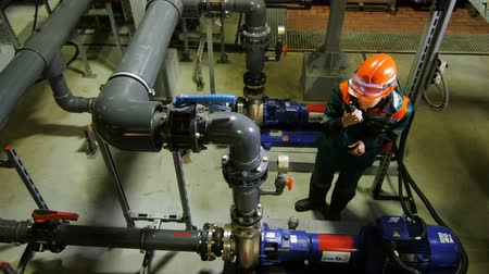 hydrocarbon : KAZAN, TATARSTAN  RUSSIA - SEPTEMBER 27 2017: Top view female worker stands among oil pipelines and reports information on radio set at workshop on September 27 in Kazan