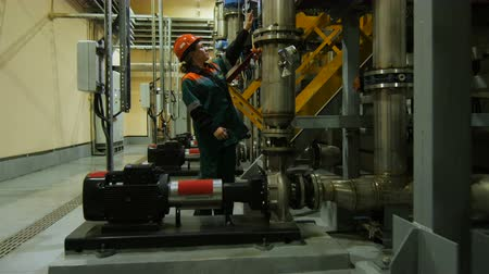 compressor : KAZAN, TATARSTAN  RUSSIA - AUGUST 22 2017: Side view of a woman engineer in helmet examines meters data on a pipeline system in modern factory on August 22 in Kazan