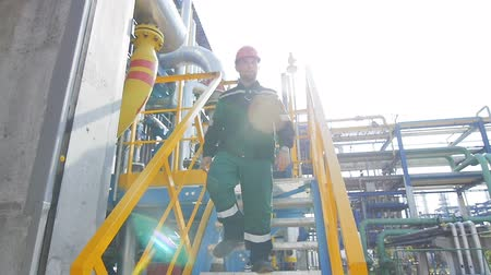 hydrocarbon : KAZAN TATARSTAN  RUSSIA - AUGUST 21 2017: Slow motion closeup oil production plant worker climbs down stairs against pipelines and constructions on August 21 in Kazan