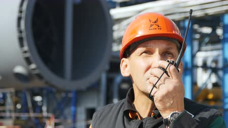 hydrocarbon : KAZAN TATARSTAN  RUSSIA - AUGUST 21 2017: Closeup employee in orange helmet inspects petrochemical plant territory and reports on portable radio on August 21 in Kazan