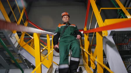 merdiven : KAZAN TATARSTAN  RUSSIA - AUGUST 21 2017: Closeup man in protective outfit climbs down stairs from workshop in oil production factory on August 21 in Kazan