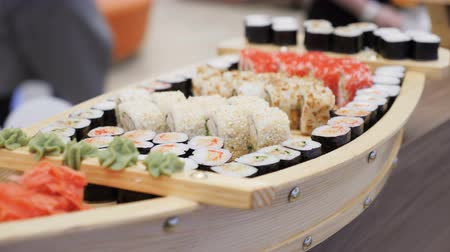 васаби : closeup delicious assorted sushi rolls with salmon and grig served on a wooden tray in a boat shape