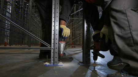 distribution lectrique : slow motion close-up of skilled workers in protective outfit work using drills to mount racks in warehouse Stock Footage