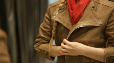 потребитель : KAZAN, TATARSTAN  RUSSIA - MARCH 02 2017: Closeup of an attractive lady in red neckerchief on a stylish light brown leather jacket in front of a mirror on March 02 in Kazan Стоковые видеозаписи