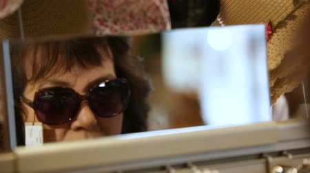 new clothes : KAZAN, TATARSTAN  RUSSIA - MARCH 02 2017: Closeup of a beautiful middle-aged woman trying on elegant sunglasses and looks at a narrow mirror in store on March 02 in Kazan