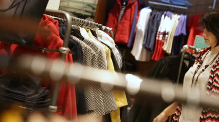 coisa : KAZAN, TATARSTAN  RUSSIA - MARCH 06 2017: Closeup of pretty brunette woman chooses new clothes sorting out suits and takes chosen thing to try on in woman boutique on March 06 in Kazan