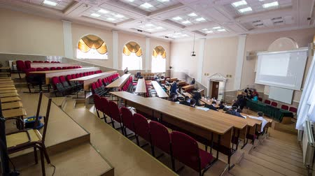 participante : KAZAN, TATARSTANRUSSIA - APRIL 04 2018: Time lapse participants come into and sit down on red chairs in large brightly lit conference hall on April 04 in Kazan Vídeos