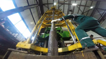 levantado : KAZAN, TATARSTANRUSSIA - APRIL 04 2018: View from below young worker in green uniform controls huge metal pin lifted up by machine in workshop on April 04 in Kazan