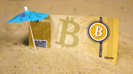 vantagem : bitcoin banknote in sand near umbrella skewer belongs to cryptocurrency presenting simply record in database