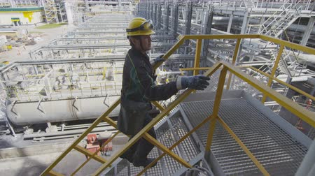 petrolkémiai : worker goes up stairs onto support ground by pipes Stock mozgókép
