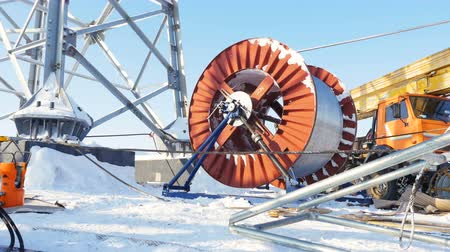 pilon : cable unwinds from huge bobbin at tower among snow Stock mozgókép