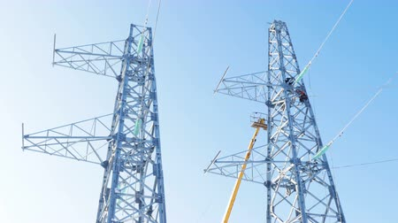voltů : worker on tower platform fixes high voltage cables