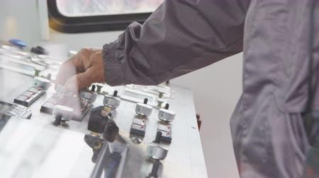 automate : Employee Hand Turns Round Levers on Control Panel Stock Footage