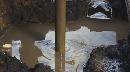 prospect : Prospecting Pit Metal Pipe Turns Round in Mud Soil Stock Footage