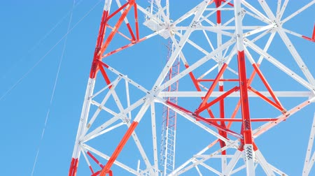 blue red : red and white lacy metal transmission tower against sky