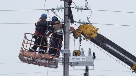 montáž : workers fix electrical equipment on support in winter