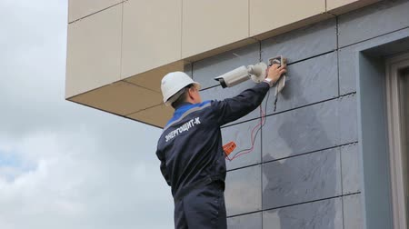 installer : technician installs outdoor surveillance camera
