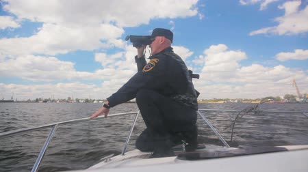 patrol : officer sits and looks through binoculars on launch Stock Footage