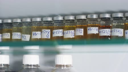 frasco pequeno : bottles with oil product samples on shelf in lab Vídeos