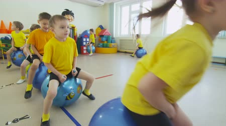mateřská škola : kids jump on inflatable rubber balls in kindergarten