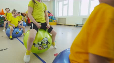 pigtail : girl jumps on inflatable rubber ball in kindergarten gym